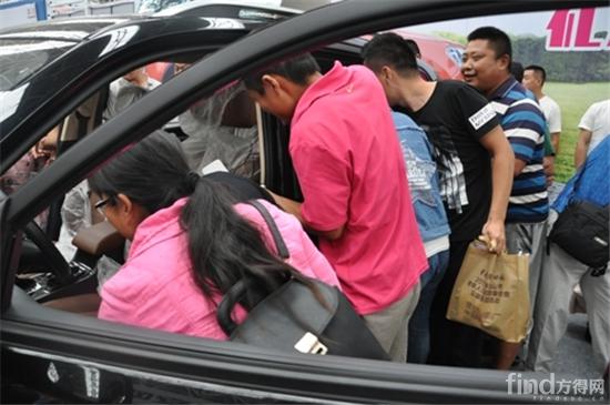 汽车奔向终点,两边围观的观众则一起为大力士们加油,活动气氛十分浓烈